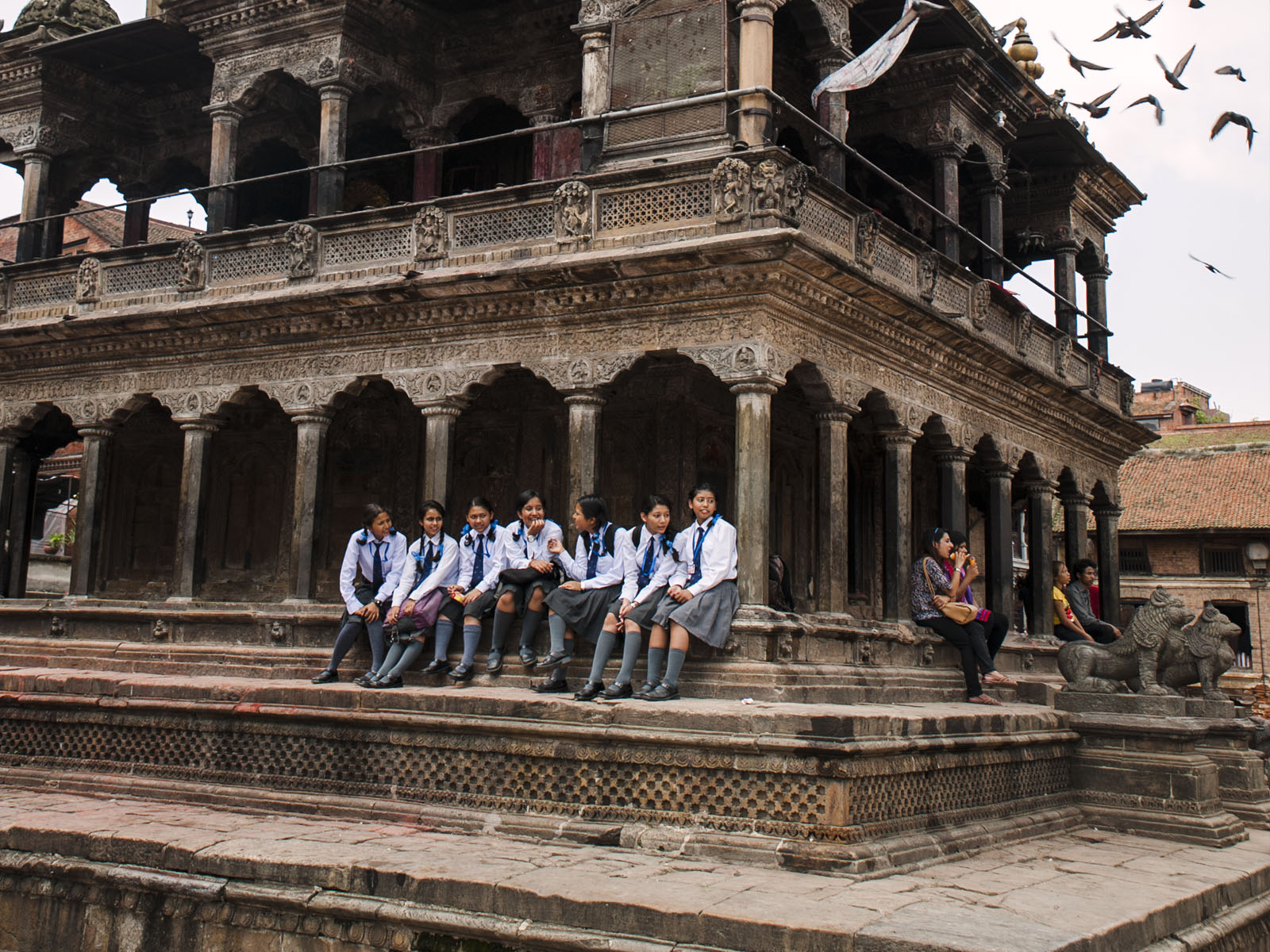 Schoolgirls take a break on one of the many temples in Durbar Square.