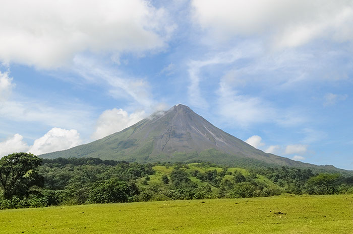 arenal-volcano-on-a-sunny-day-in-costa-rica-with-forest-and-field-in-foreground
