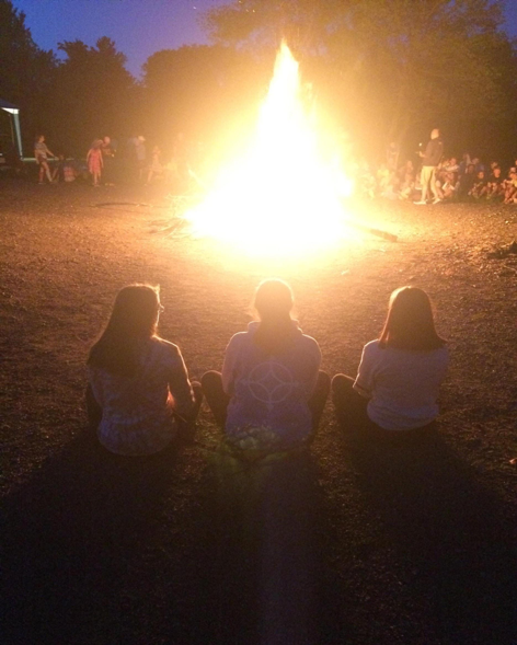 girls watching a campfire