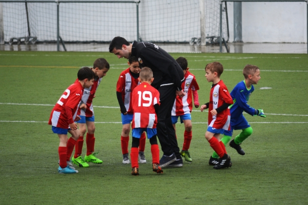 coach teaching kids to play soccer