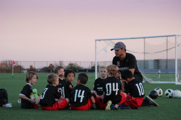 child team listening to coach of soccer team